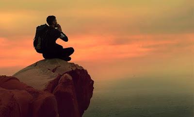 man sitting alone on mounain