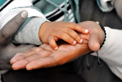 Childs hand on parents hand