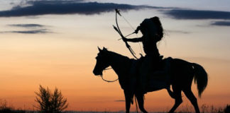 A man on horse with bow and arrow