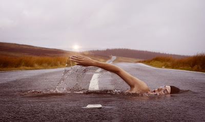 Man swimming across road
